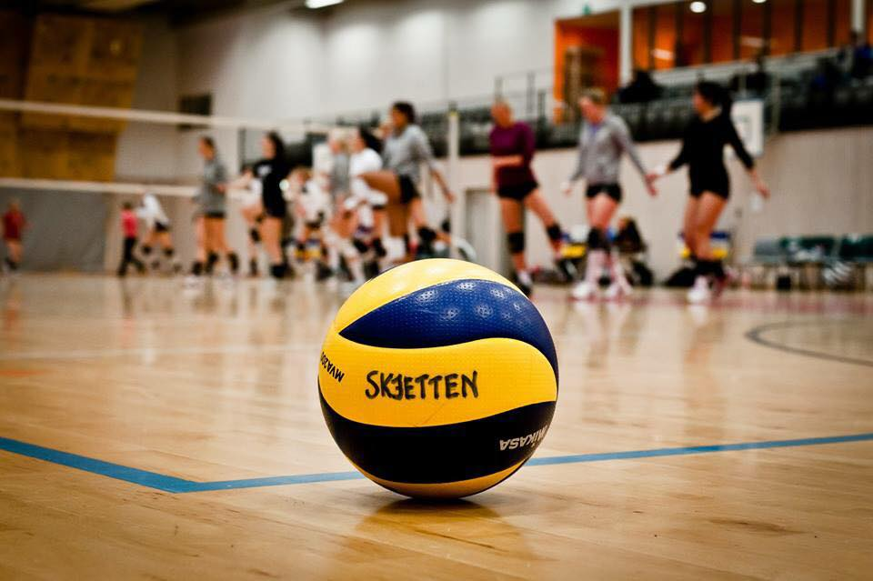Ball på gulv med volleyballspillere i bakgrunn